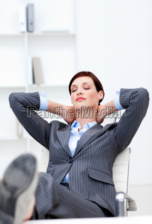 young businesswoman sleeping with feet on