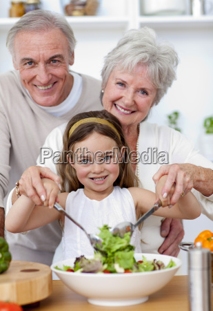 smiling grandparents eating a salad with