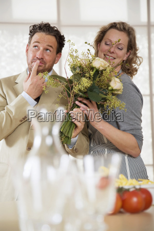 mature couple in kitchen with flower