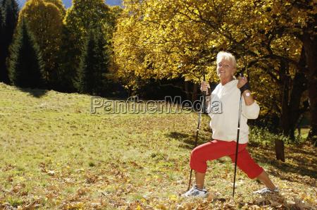 senior woman holding hiking pole exercising