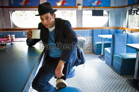 man, in, fedora, sitting, at, diner - 3008359