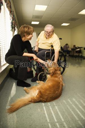 elderly man with woman petting dog