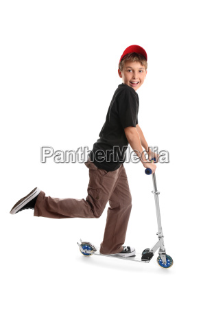 child riding a scooter and smiling