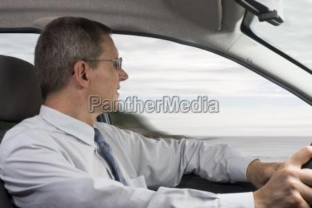 businessman drives car at the seashore