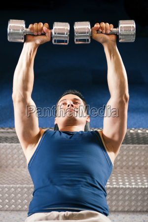 man, lifts, dumbbells, in, the, studio - 3079525