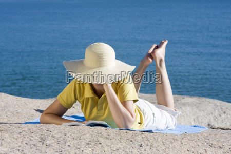 woman reading book by the sea