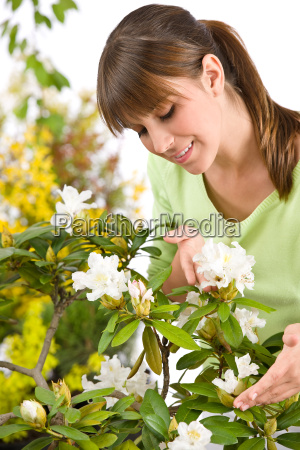 portrait of woman smelling blossom of