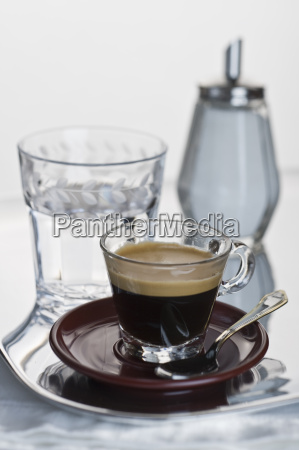 espresso in glass cup on red