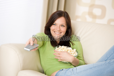 woman watching television with popcorn in