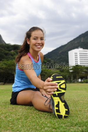 sporty woman stretches in the park