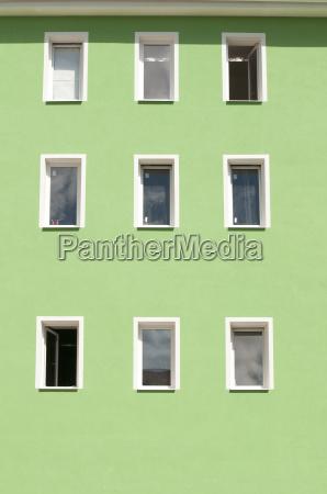 row of windows on green wall