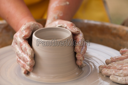 two hands make pottery a bowl
