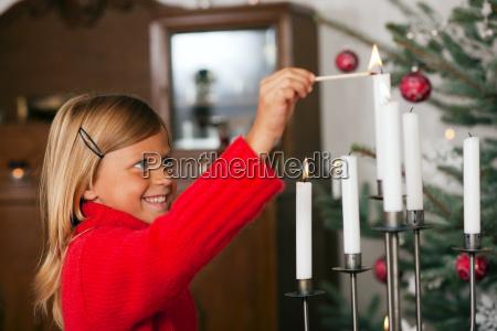 child ignites christmas candles