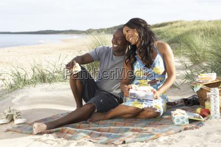 young couple enjoying picnic on beach