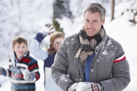 father and children having snowball fight