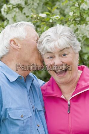 senior man whispering into ear of