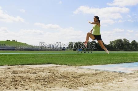 woman doing long jump