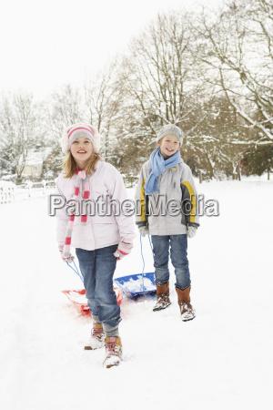 children pulling sledge through snowy landscape