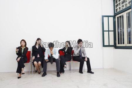 two businessmen and three businesswomen sitting