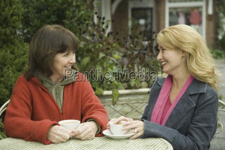 two mature women having tea and