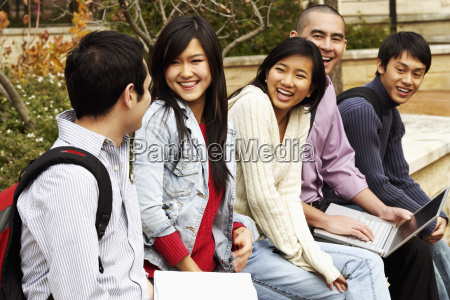 five young college students sitting together