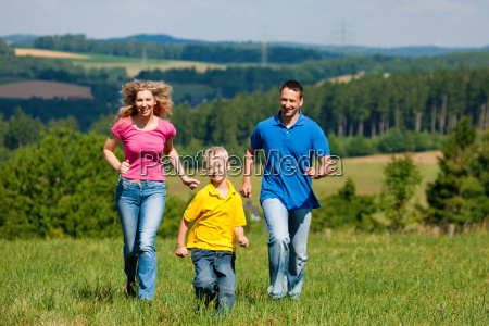 family playing catch in the meadow