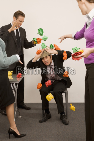 businessman protecting himself from colleagues throwing