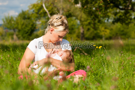 mother nursing baby on meadow