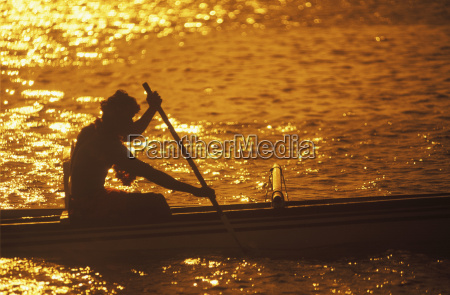 silhouette of a person rowing a