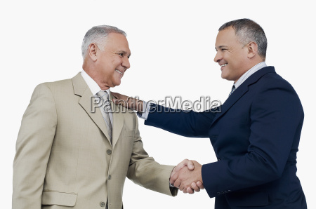 two businessmen shaking hands and smiling