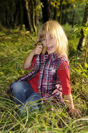 little girl collects mushrooms