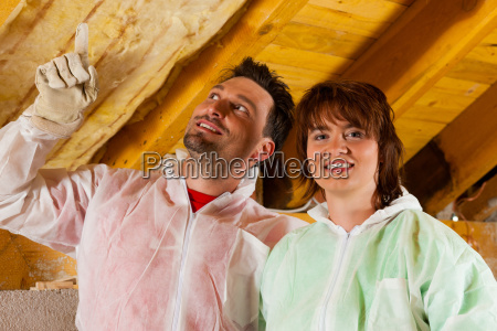 couple brings insulation on roof at