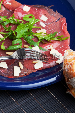 carpaccio on a blue plate with