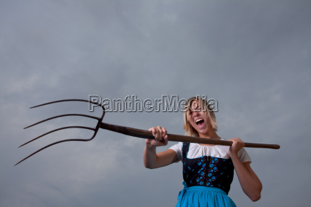 wuetendes bayerisches maedchen mit einer mistgabel