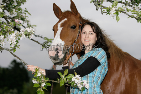 woman snuggles with horse