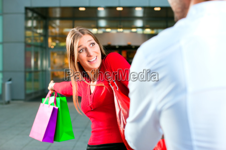 woman pulling man in shopping center