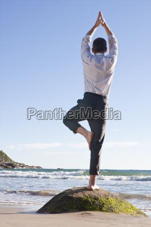 businessman is balancing on one leg