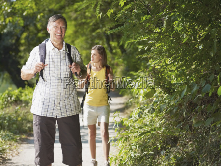 grandfather and grandaughter hiking in wood