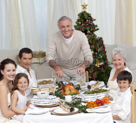 grandfather cutting turkey for christmas dinner