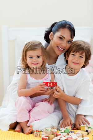smiling siblings and their mother playing