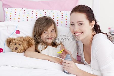 sick little girl in bed taking