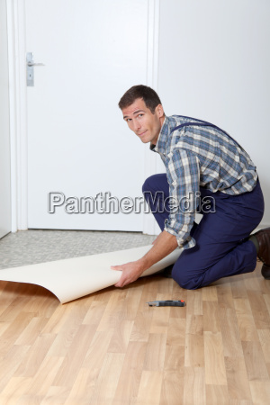 artisan putting linoleum on the floor