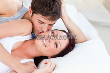 caring caucasian couple lying on bed