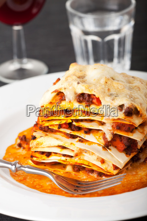 closeup of lasagna with red wine
