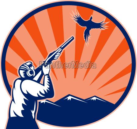 hunter aiming shotgun rifle at bird