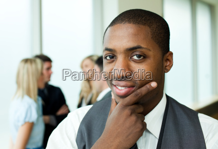 thoughtful ethnic businessman in office smiling