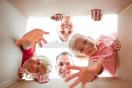 joyful family unpacking boxes in their