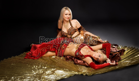 two young woman lay on gold