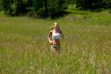 young woman jogging in a meadow