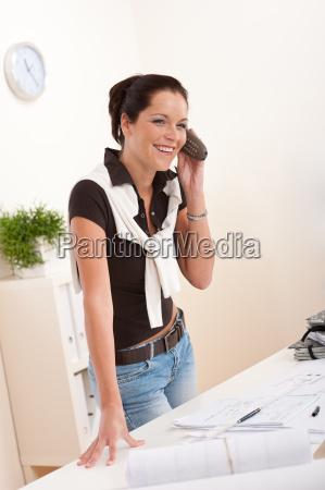 smiling female architect with telephone